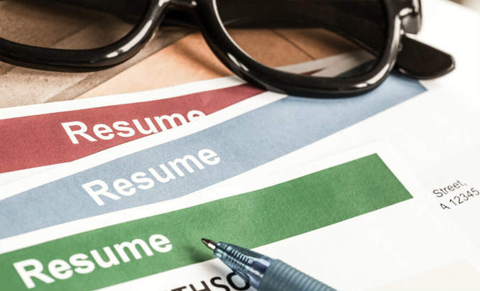 Resumes with pen and glasses