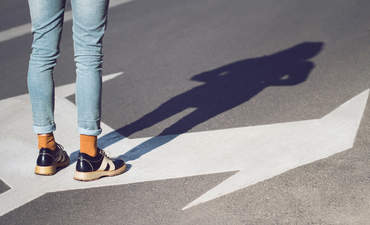Close up side view of person wearing black shoes and blue jeans standing on a street with arrow signs pointing in different directions
