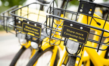 Close up on the handle bar basket with 'Share More Consume Less' sign, on a yellow Ofo bike, part of an app based bicycle sharing network.