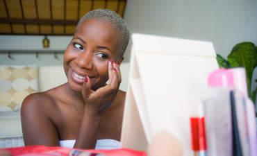 Black person applying makeup cosmetics using fingers