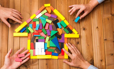 Building blocks shaped like a house, with hands on them