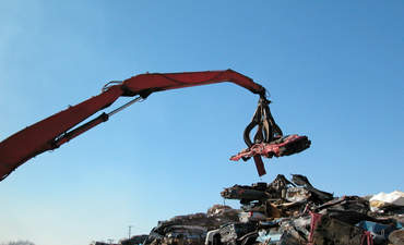Claw crane picking up an old car to be recycled in a scrap yard