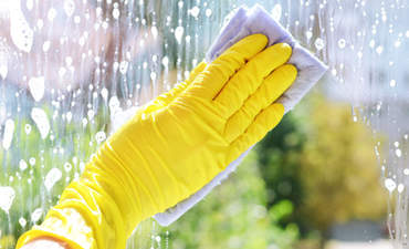 Gloved hand cleaning a window
