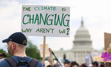 Person holding sign at People's Climate March in April 2017