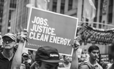 Black and white image of a person carrying a placard supporting 'Jobs, Justice, Clean Energy' during the 2014 People's Climate March, New York