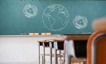 A classroom's chalkboard with an earth on it