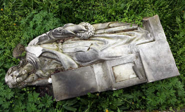 A fallen tombstone angel in the grass