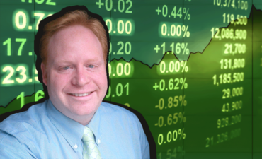 Evan Harvey, sustainability at NasDaq, in front of a stock exchange board