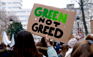Climate March sign that says Green Not Greed
