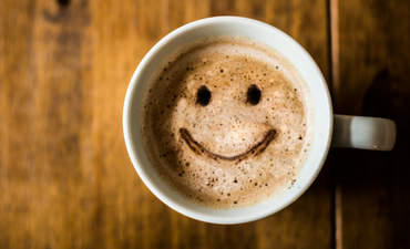 A mug with a smiley face drawn in the coffee.