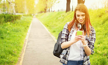 Oblivious young woman staring at phone in a park