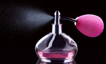 Image of perfume bottle spraying bright pink liquid