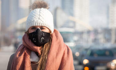 Young woman wearing protective mask in the city street, smog and air pollution during winter