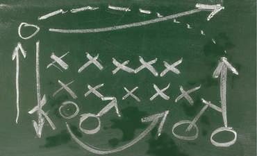 Illustration of a football field play on a chalkboard