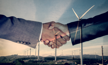 Business people shaking hands in front of wind turbines