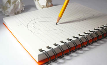 Pencil sketching a question mark on a notepad