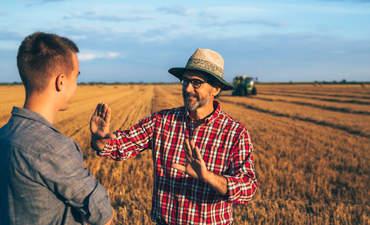 Two ranchers talking in a wheat field