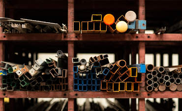 Different styles and sizes of old recycled metal pipes and construction materials laying on a shelf rack.
