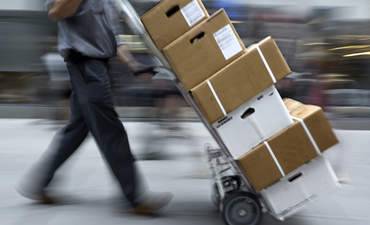 Delivery person with boxes on a dolly