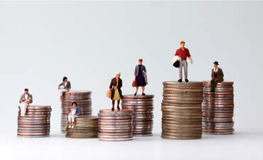 Miniature people standing on piles of different heights of coins.