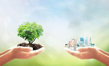 Two human hand holding heart shape of tree and big city over blurred green nature background
