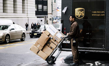 UPS delivery worker waiting by his truck to cross the street holding a cart full with packages in New York