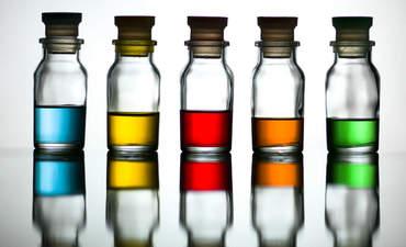 Five vials of brightly colored liquids