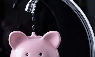 Water being poured into a piggybank