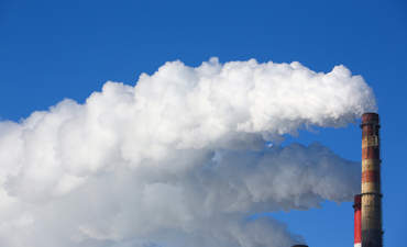 White smoke comes from pipes against blue sky