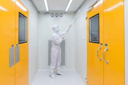 A person in sterile coverall gown using cleaning tool in cleanroom facility.