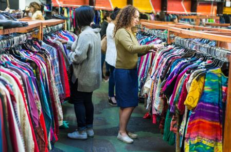 Shoppers browsing through clothing in a thrift store.