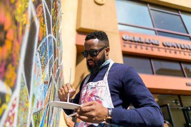 Man painting at the art wall