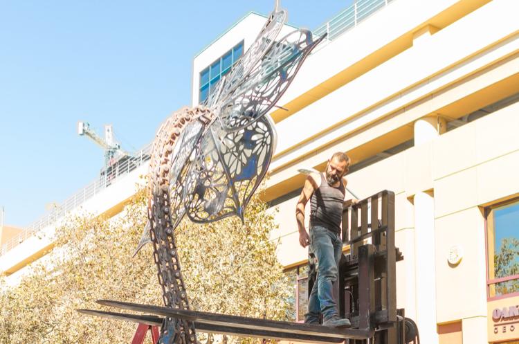 Metal flower statue getting installed using forklift
