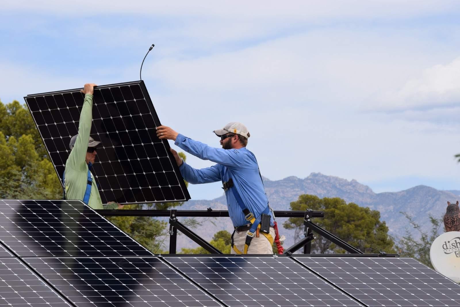 Lead installer Travis Kendall, helping install solar panels