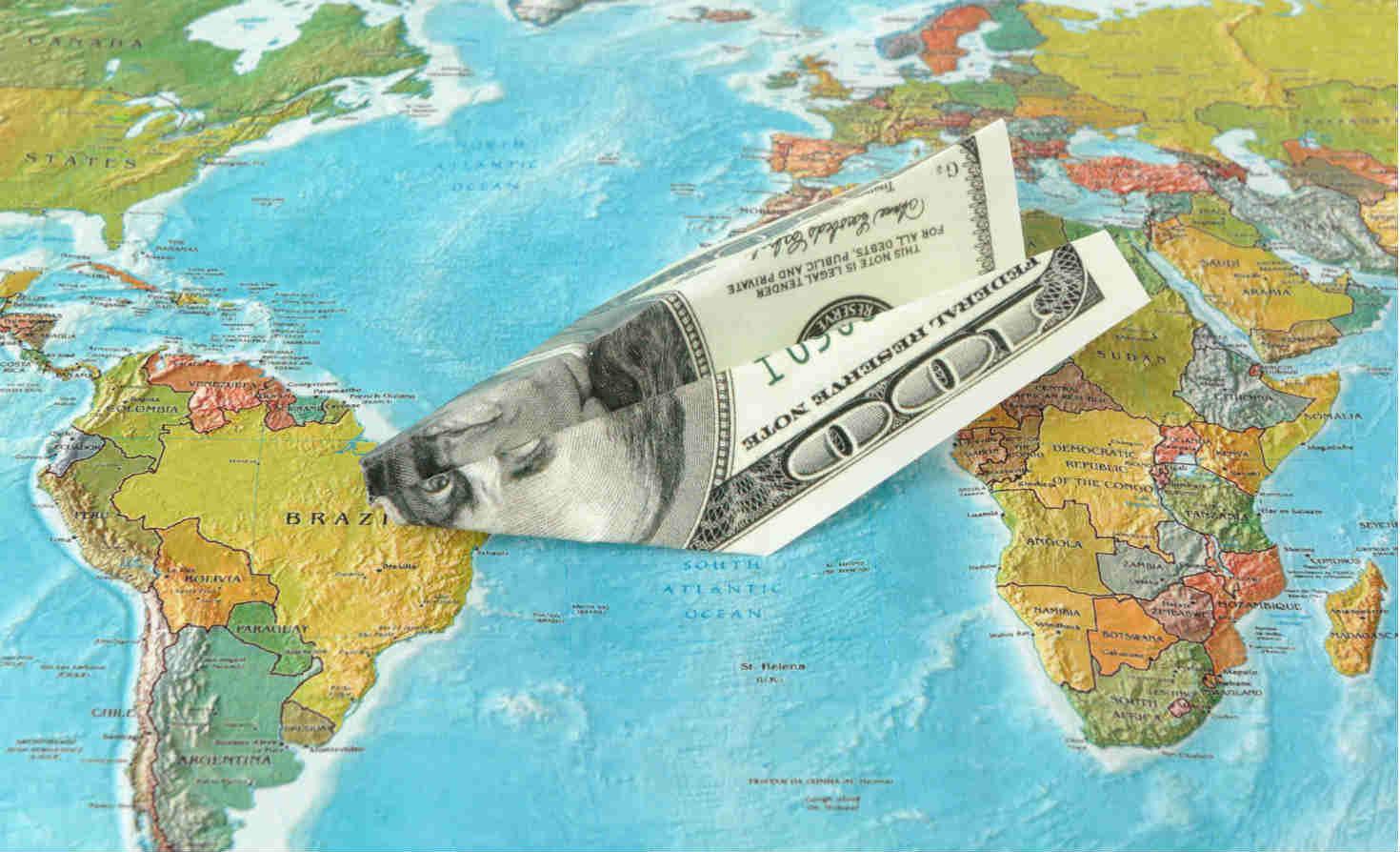 $100-bill paper plane on globe