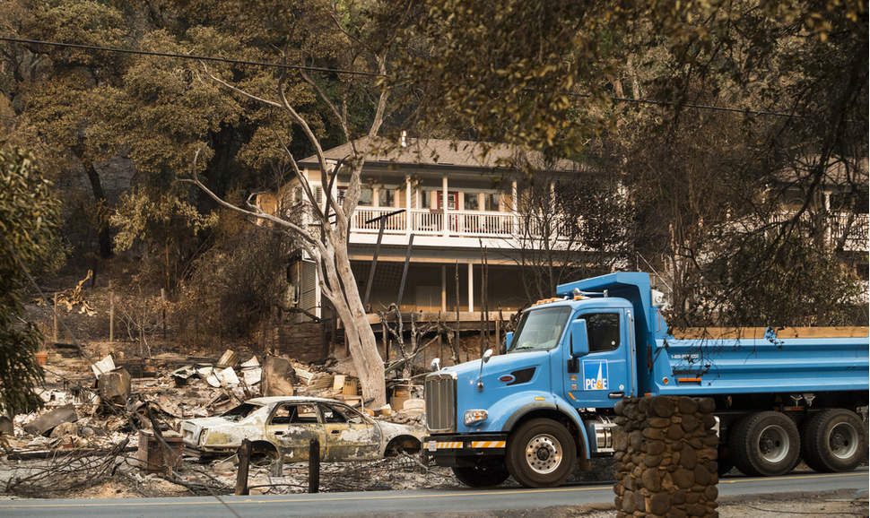 A PG&E truck drives through a Sonoma County, California, neighborhood devastated by fires