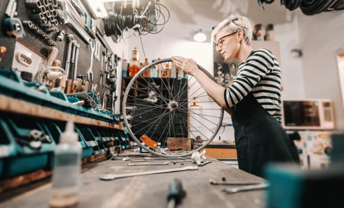 Person repairing wheel in bike shop