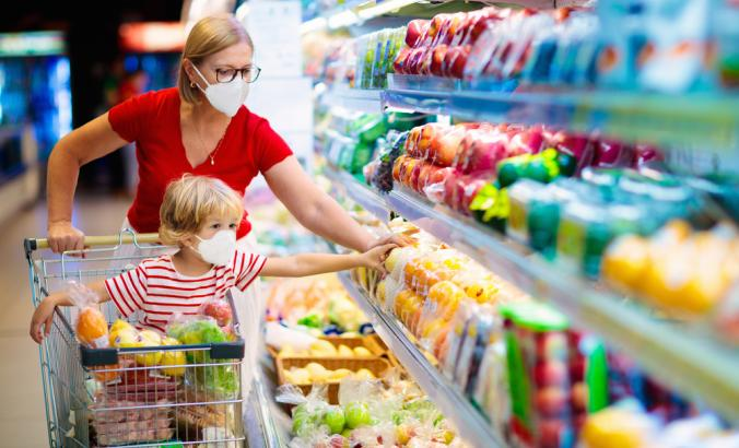 Parent and child wearing surgical face masks while shopping for produce in supermarket.