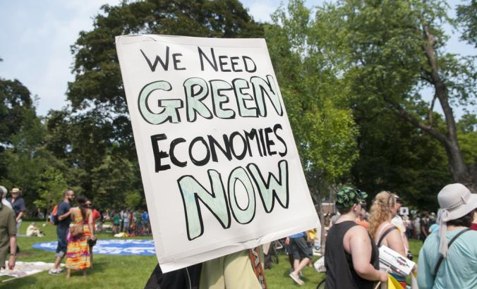 "Person holds sign that reads ""We need green economies now"""