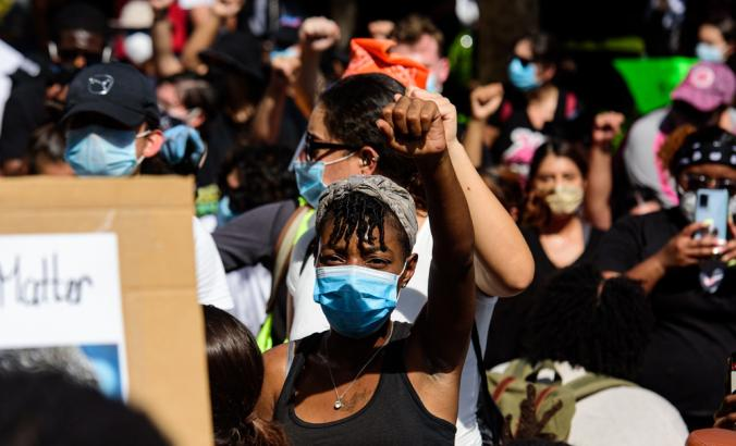 Black person wearing mask and leading a group of demonstrators on a road in downtown Miami, Florida.
