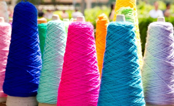 Rows of colorful thread on spools