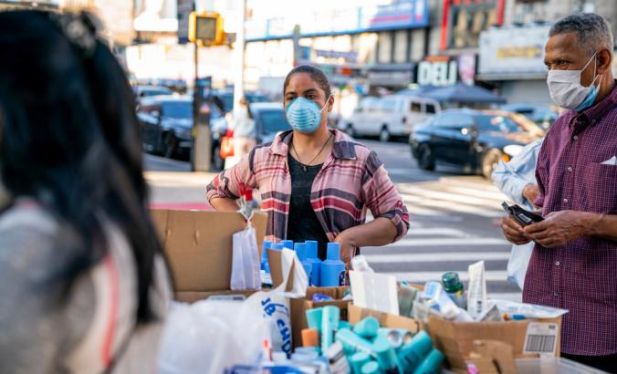Person wearing a mask sells beauty products at a street stall in Washington Heights, Manhattan in New York City during the COVID-19 pandemic.