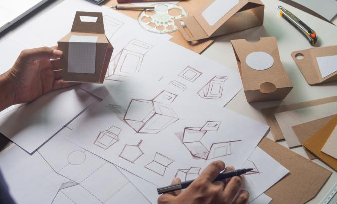 Person designing cardboard packaging and holding mockup for the design.