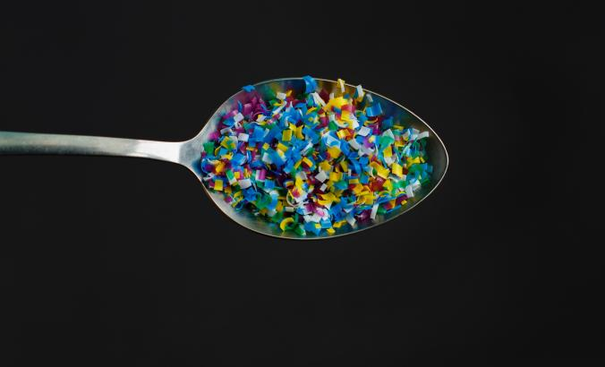 Multicolored plastic pellets served on a spoon.