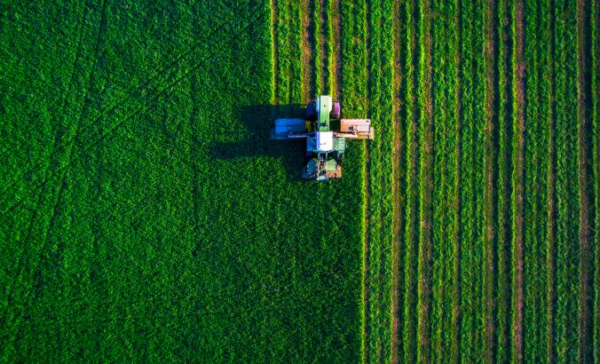 Aerial view of tractor working in a green field