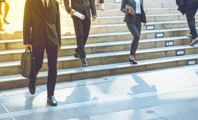 Businesspeople walking on steps. They hold hold briefcases and folders in their hands..
