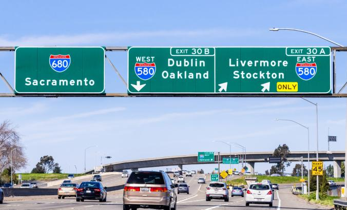 Freeway interchange in East San Francisco Bay Area; Signs towards Sacramento, Oakland, Stockton and other destinations, guiding drivers to the right lane