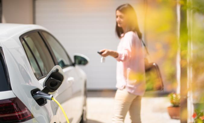 Close up of a electric car charger with person in the background, locking a car