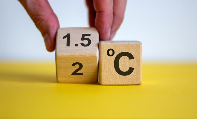 A person's hand turning a cube and changes the expression '2 C' to '1.5 C', or vice versa.