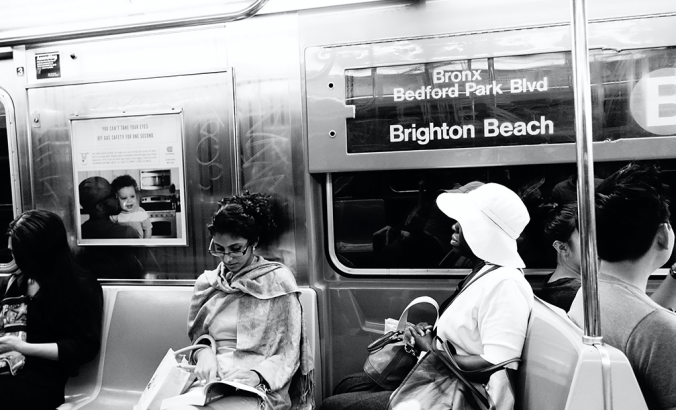 In New York City, three commuters can be seen riding the B train. The photo is black and white.